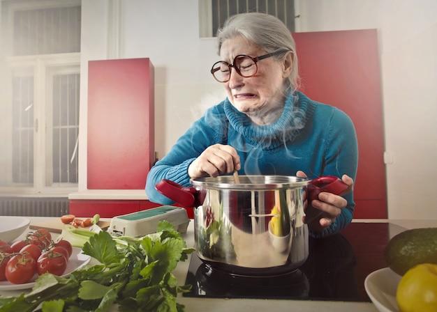 Ältere frau, die schlechtes etwas schmeckt