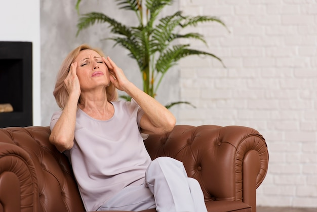 Ältere frau, die schrecklichen kopfschmerzen hat