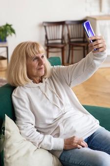 Ältere frau, die selfie mit smartphone zu hause nimmt