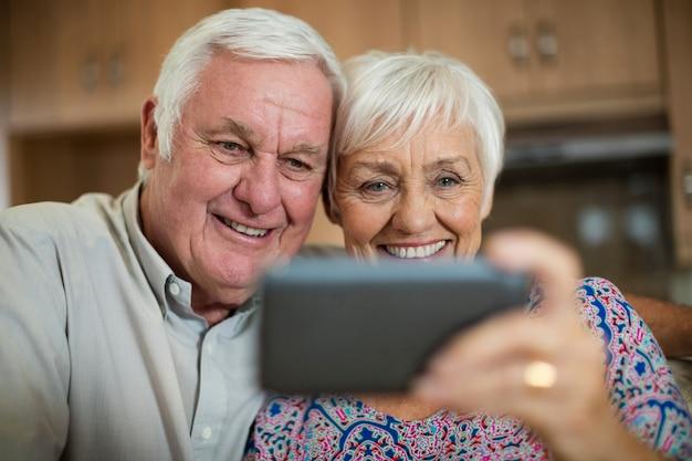 Ältere frau, die selfie vom handy in der küche zu hause nimmt