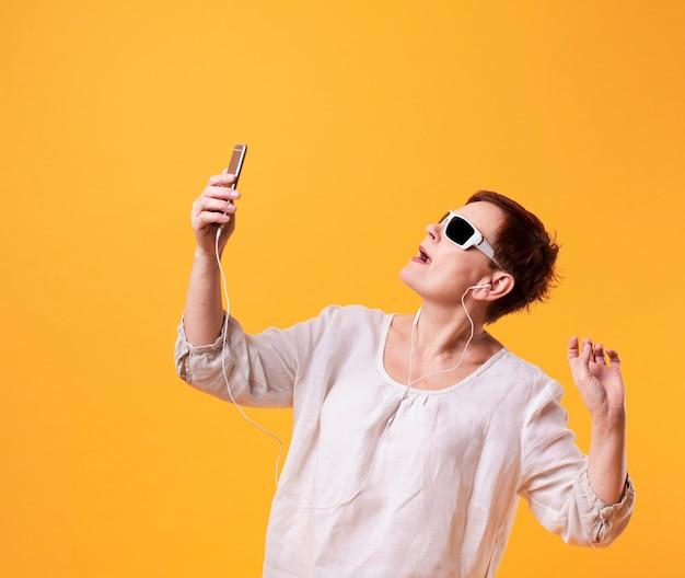 Ältere frau, die selfies auf gelbem hintergrund nimmt