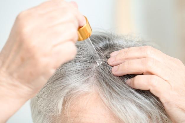Ältere frau, die serum für haarausfallbehandlung verwendet