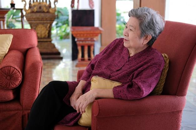 Ältere frau, die sich auf sofa-couch im wohnzimmer entspannt