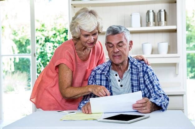 Ältere frau, die sich bei tisch mit ehemann auf dokumenten bespricht