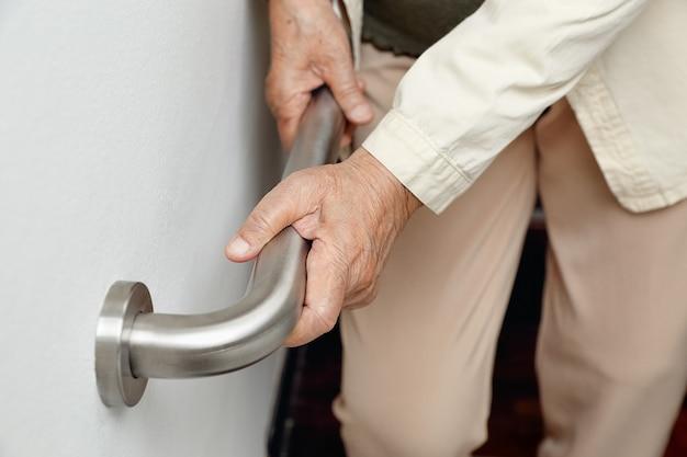 Ältere frau, die sich für sicherheitsschritte am handlauf festhält