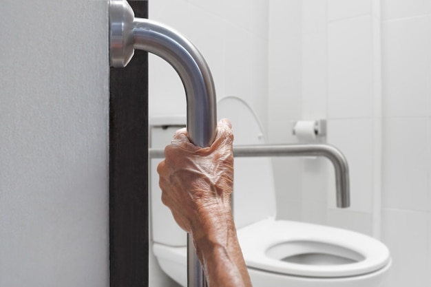 Ältere frau, die sich im badezimmer am handlauf festhält
