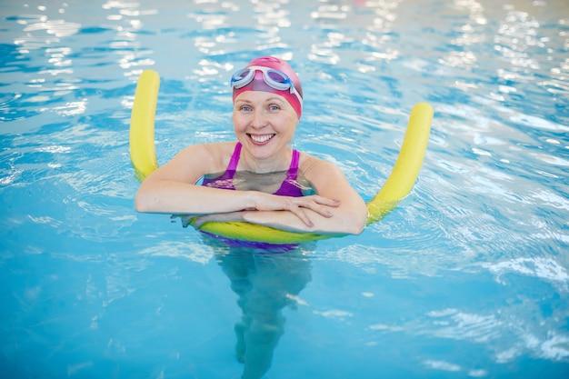 Ältere frau, die sich im schwimmbad entspannt
