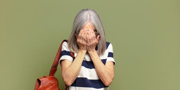 Ältere frau, die sich traurig, frustriert, nervös und depressiv fühlt, das gesicht mit beiden händen bedeckt und weint