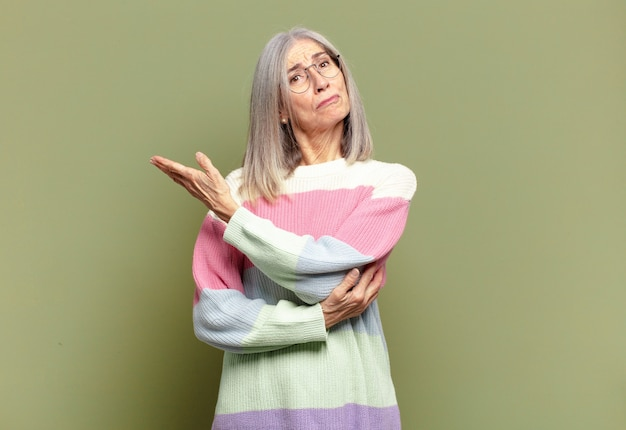 Ältere frau, die sich verwirrt und ahnungslos fühlt und sich über eine zweifelhafte erklärung oder einen zweifelhaften gedanken wundert