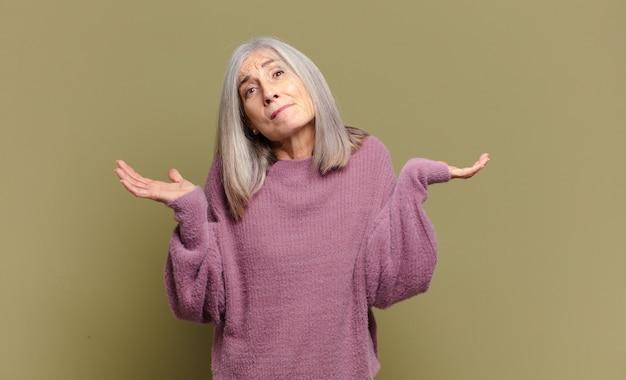 Ältere frau, die sich verwirrt und verwirrt fühlt, zweifelt, gewichtet oder verschiedene optionen mit lustigem ausdruck wählt
