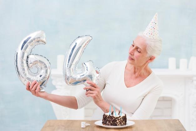 Ältere frau, die silbernen folienballon auf ihrem 64. geburtstag betrachtet
