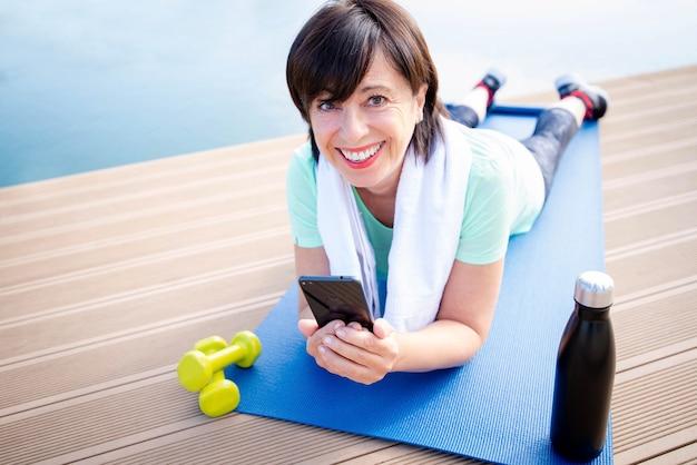 Ältere frau, die smartphone-gerätetraining-fitness-training im freien hält