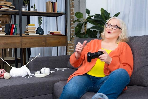 Ältere frau, die spielstation mit freudenauflagen spielt