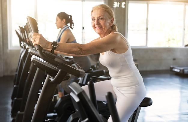 Ältere frau, die spinnendes fahrrad in der eignungsturnhalle ausübt. älteres gesundes lebensstilkonzept.
