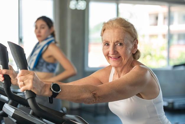 Ältere frau, die spinning-fahrrad im fitnessstudio trainiert. älteres gesundes lebensstilkonzept.