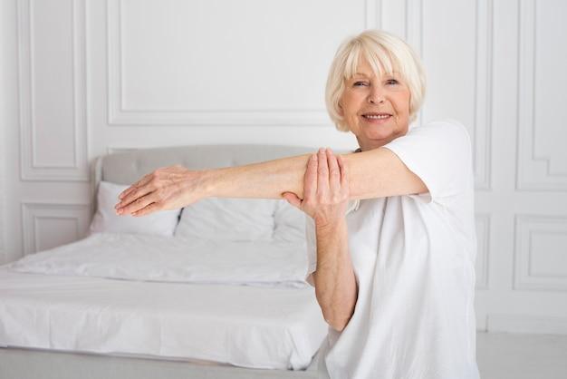 Ältere frau, die sport im schlafzimmer tut
