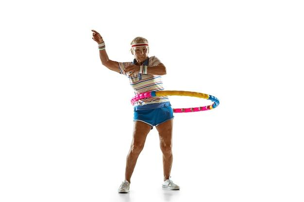 Ältere frau, die sportbekleidungstraining mit reifen auf weißer wand trägt