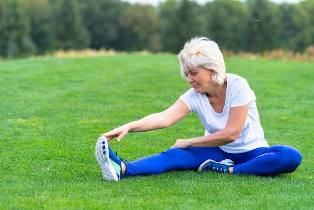 Ältere frau, die sportkleidung trägt, die auf grünem gras im park ausübt