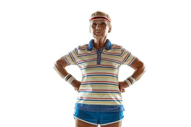 Ältere frau, die sportkleidungstraining trägt und auf weißer wand aufwirft