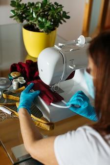 Ältere frau, die stoffgesichtsmasken für das spenden näht