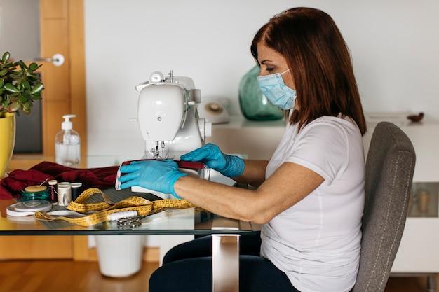 Ältere frau, die stoffgesichtsmasken für freunde und familie näht
