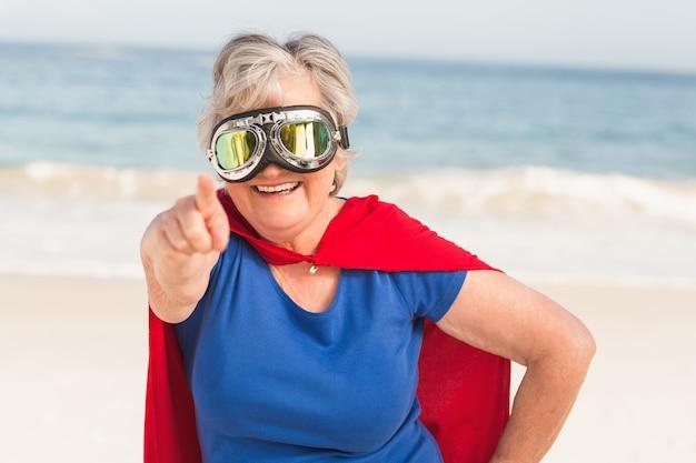 Ältere frau, die superfrau custome trägt