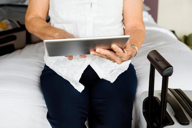 Ältere frau, die tablette auf einem bett verwendet