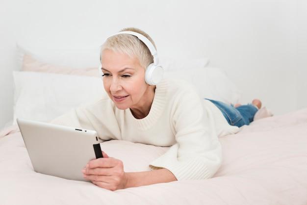 Ältere frau, die tablette betrachtet und musik auf kopfhörern hört