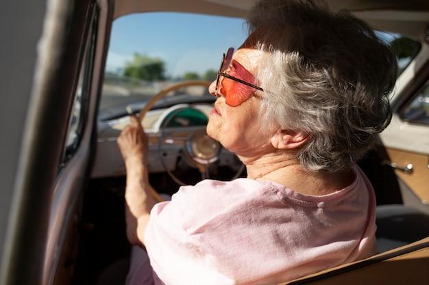 Ältere frau, die tagsüber mit dem auto reist Kostenlose Fotos