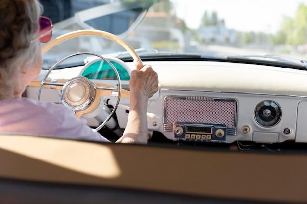 Ältere frau, die tagsüber mit dem auto reist