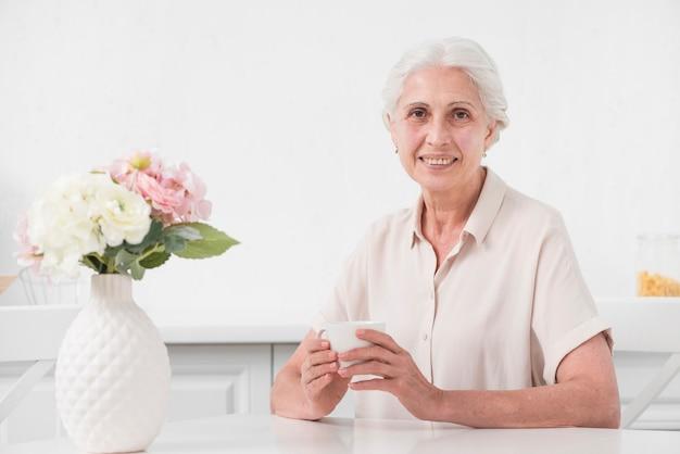 Ältere frau, die tasse kaffee mit blumenvase auf weißer tabelle hält