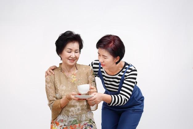 Ältere frau, die tee mit ihrer tochter trinkt, kümmern sich, lokalisiert auf weiß