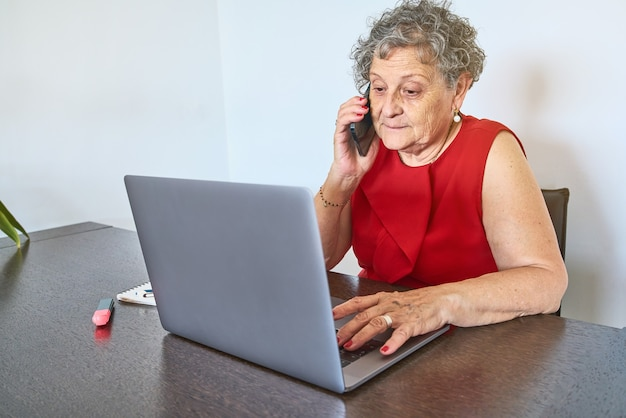 Ältere frau, die telefoniert, während sie zu hause einen laptop benutzt