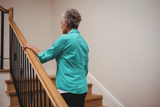 Ältere frau, die treppe hinaufgeht