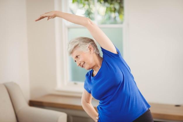 Ältere frau, die übung zu hause ausdehnend durchführt