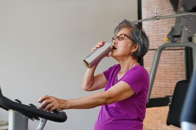 Ältere frau, die übungen im fitnessstudio macht
