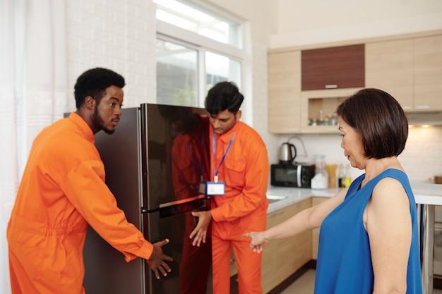 Ältere frau, die umzugsunternehmen sagt, wo sie ihren neuen großen kühlschrank in ihre küche stellen sollen