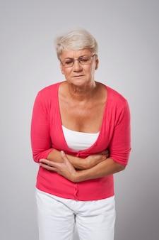 Ältere frau, die unter bauchschmerzen leidet
