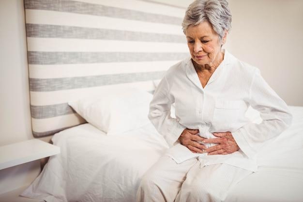 Ältere frau, die unter den magenschmerzen sitzen auf bett im schlafzimmer leidet