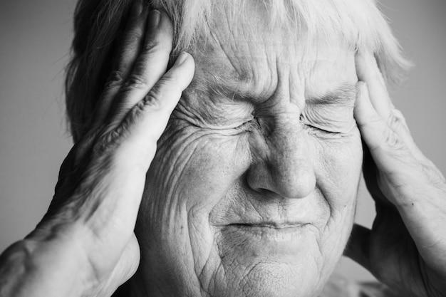 Ältere frau, die unter migräne leidet