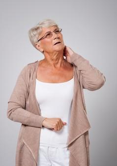 Ältere frau, die unter nackenschmerzen leidet