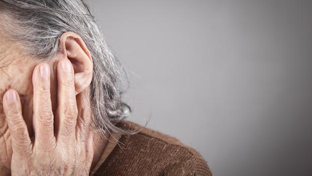 Ältere frau, die unter ohrenschmerzen leidet.