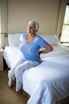 Ältere frau, die unter rückenschmerzen im schlafzimmer zu hause leidet
