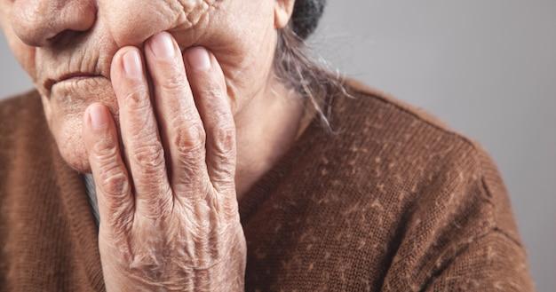 Ältere frau, die unter zahnschmerzen leidet.