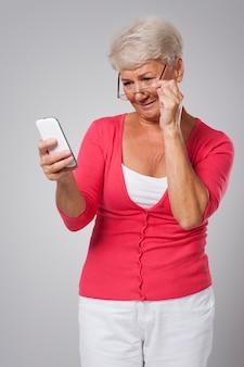 Ältere frau, die versucht, zeitgenössisches mobiltelefon zu verwenden