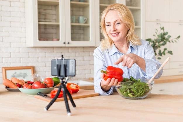 Ältere frau, die videoanruf am handy zeigt grünen pfeffer beim zubereiten des salats macht