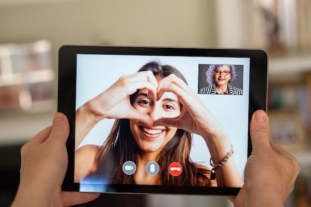 Ältere frau, die videoanruf mit ihrer enkelin auf tablette hat