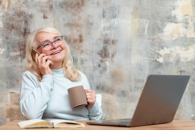 Ältere frau, die vom haus arbeitet