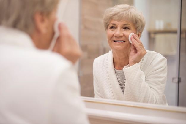 Ältere frau, die vor dem spiegel steht