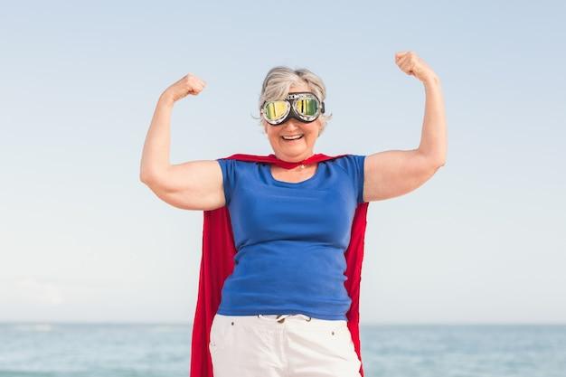 Ältere frau, die vorgibt, ein superheld zu sein